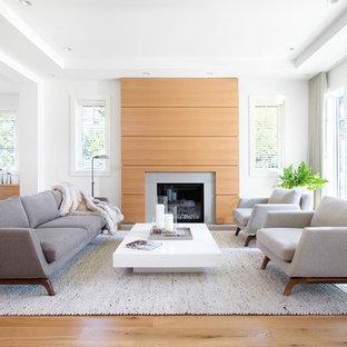 Ejemplo de salón para visitas abierto, actual, de tamaño medio, sin televisor, con paredes blancas, suelo de madera en tonos medios, chimenea tradicional, marco de chimenea de baldosas y/o azulejos y suelo marrón