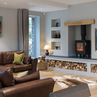 Inspiration for a classic living room in Other with grey walls, light hardwood flooring, a wood burning stove, a wall mounted tv and beige floors.