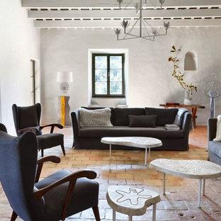 Modelo de salón para visitas bohemio, sin chimenea, con paredes blancas y suelo de baldosas de terracota