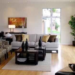 Esempio di un soggiorno contemporaneo di medie dimensioni e chiuso con pareti bianche, pavimento in bambù, camino sospeso, cornice del camino in metallo e nessuna TV