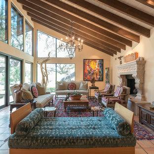 Ejemplo de salón para visitas abierto, bohemio, extra grande, con marco de chimenea de piedra, suelo de baldosas de terracota, chimenea tradicional, suelo naranja y paredes beige