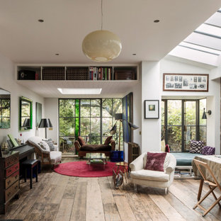 Inspiration for an eclectic open plan living room in London with brown walls, medium hardwood flooring and brown floors.