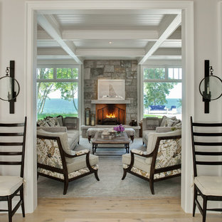 Example of a beach style light wood floor living room design in Chicago with gray walls, a stone fireplace and a standard fireplace