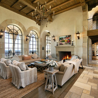 Inspiration for a large mediterranean formal and open concept limestone floor and beige floor living room remodel in Santa Barbara with beige walls, a standard fireplace, a stone fireplace and no tv