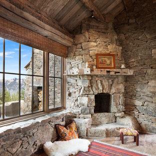 Foto de salón rural con suelo de piedra caliza, chimenea de esquina y marco de chimenea de piedra