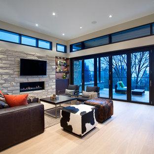 Foto di un soggiorno design con sala formale, cornice del camino in pietra e TV a parete