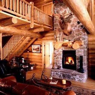 Свежая идея для дизайна: большая парадная, открытая гостиная комната в стиле рустика с коричневыми стенами, темным паркетным полом, стандартным камином, фасадом камина из камня и коричневым полом - отличное фото интерьера