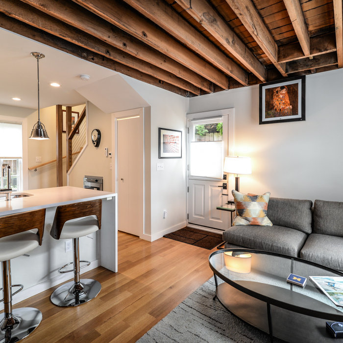 Inspiration for a small rustic loft-style and formal medium tone wood floor and brown floor living room remodel in Detroit with gray walls, no fireplace and a wall-mounted tv
