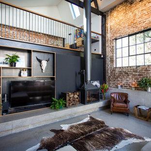 シドニーの巨大なインダストリアルスタイルのおしゃれなリビングロフト (黒い壁、コンクリートの床、コーナー設置型暖炉、コンクリートの暖炉まわり、埋込式メディアウォール) の写真