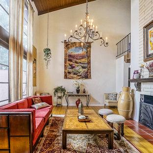 Esempio di un grande soggiorno etnico aperto con pareti beige, parquet chiaro, camino classico, cornice del camino in pietra, parete attrezzata e pavimento marrone