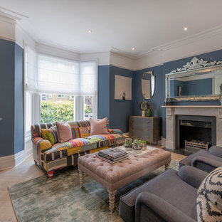Classic open plan living room in London with blue walls, light hardwood flooring, a standard fireplace and beige floors.