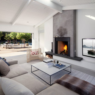 Design ideas for a scandinavian living room in Santa Barbara with white walls, a standard fireplace and a wall mounted tv.