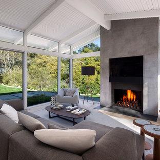 Esempio di un soggiorno moderno aperto con pavimento in legno massello medio, camino classico e TV a parete