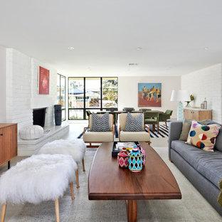 Réalisation d'un salon vintage ouvert avec un mur blanc, béton au sol, une cheminée standard, un manteau de cheminée en brique, un téléviseur encastré et un sol gris.