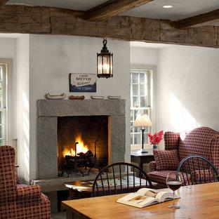 Bild på ett lantligt allrum med öppen planlösning, med mellanmörkt trägolv, vita väggar, en standard öppen spis och en spiselkrans i tegelsten