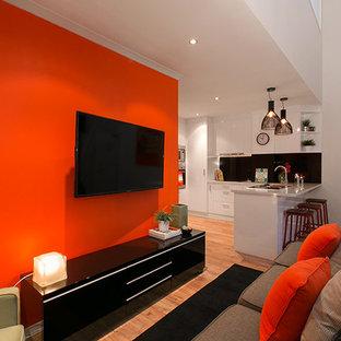 Immagine di un soggiorno minimalista di medie dimensioni e stile loft con pareti arancioni, TV a parete e pavimento in bambù