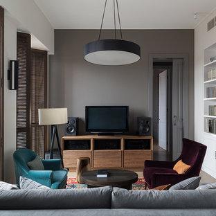 Идея дизайна: гостиная комната в современном стиле с серыми стенами и отдельно стоящим ТВ