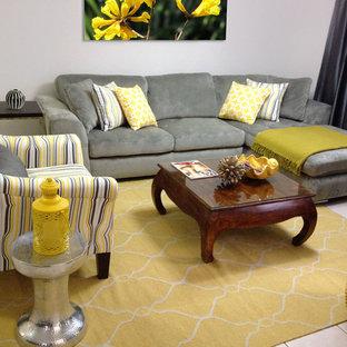 他の地域の中くらいのエクレクティックスタイルのおしゃれなLDK (グレーの壁、セラミックタイルの床、据え置き型テレビ、ベージュの床) の写真