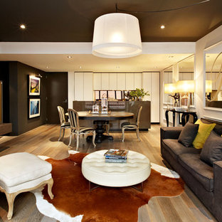 Immagine di un piccolo soggiorno contemporaneo aperto con pavimento in legno massello medio, pareti grigie, nessun camino e TV nascosta