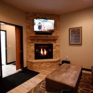 Foto di un piccolo soggiorno chic chiuso con pareti beige, pavimento in gres porcellanato, camino ad angolo, cornice del camino in pietra, TV a parete e pavimento beige