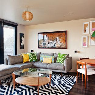 Immagine di un piccolo soggiorno moderno aperto con pareti beige e parquet scuro