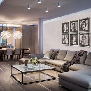 Imagen de salón abierto, contemporáneo, grande, con paredes beige y suelo de madera clara
