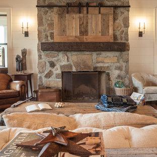 Esempio di un soggiorno country di medie dimensioni e chiuso con pareti bianche, camino classico, cornice del camino in pietra, TV nascosta, sala formale, parquet scuro e pavimento bianco