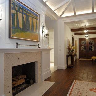 マイアミの大きいトロピカルスタイルのおしゃれなLDK (フォーマル、白い壁、濃色無垢フローリング、標準型暖炉、タイルの暖炉まわり、テレビなし、茶色い床) の写真