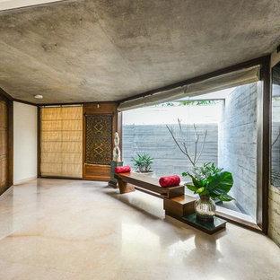 Asiatisk inredning av ett allrum med öppen planlösning, med vita väggar, betonggolv och grått golv