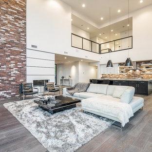 Esempio di un grande soggiorno minimalista stile loft con sala formale, pareti multicolore, parquet scuro, camino bifacciale, cornice del camino piastrellata e TV a parete