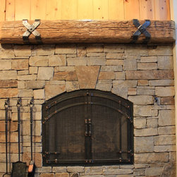 Arched top craftsman grid - Arched top fireplace doors with craftsman grid accent. Hand forged fire tool set with stone mounted hooks. Hammered criss cross mantel straps.