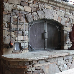 Arched top gusset corner - Arched top fireplace doors with gusset corner detail. Hand forged fire tool set with stone mounted hooks.