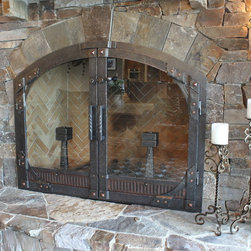 Arched top gusset, custom vent, glass - Arched top fireplace doors with copper rivets and pyramid clavos, Copper sliding vent. Glass doors with heavy latch. Custom heavy twisted handles.