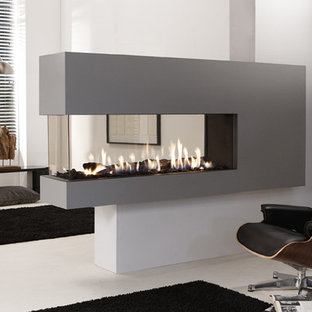 Photo of a large contemporary enclosed living room in London with a two-sided fireplace and a stone fireplace surround.