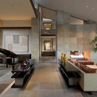 Foto di un ampio soggiorno stile americano con sala della musica, pareti beige, camino bifacciale, nessuna TV e pavimento in pietra calcarea