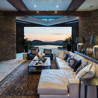 フェニックスのサンタフェスタイルのおしゃれなLDK (茶色い壁、壁掛け型テレビ、ベージュの床) の写真