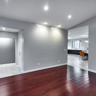This is an example of a large contemporary formal enclosed living room in San Francisco with grey walls, dark hardwood floors, no fireplace and red floor.