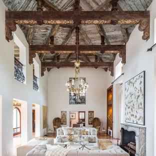 Offenes, Großes, Repräsentatives, Fernseherloses Mediterranes Wohnzimmer mit weißer Wandfarbe, Terrakottaboden, Kamin, rotem Boden und Kaminumrandung aus Stein in Los Angeles
