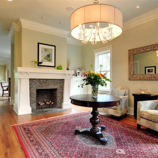 Example of a classic medium tone wood floor living room design in Atlanta with a standard fireplace and a tile fireplace