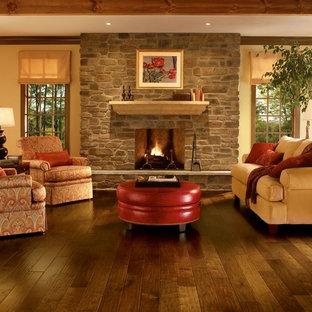 Immagine di un soggiorno classico di medie dimensioni e chiuso con pareti gialle, pavimento in legno massello medio, camino classico, cornice del camino in pietra e nessuna TV
