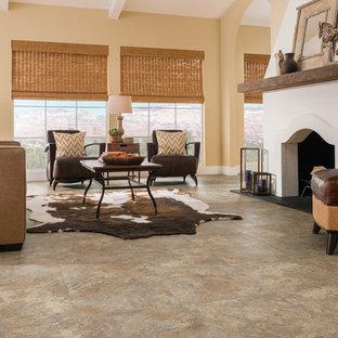 Aménagement d'un grand salon sud-ouest américain ouvert avec une salle de réception, un mur jaune, un sol en vinyl, une cheminée standard et aucun téléviseur.