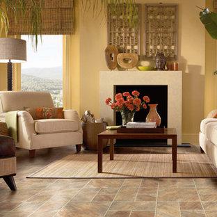 Immagine di un soggiorno tropicale di medie dimensioni e aperto con pareti gialle, sala formale, pavimento in linoleum, camino classico, cornice del camino in cemento e nessuna TV