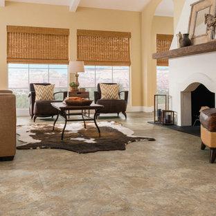 Cette image montre un grand salon sud-ouest américain fermé avec une salle de réception, un mur jaune, un sol en vinyl, une cheminée standard, aucun téléviseur et un sol marron.