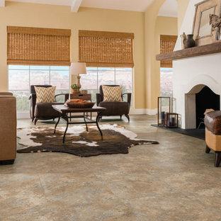 Aménagement d'un salon sud-ouest américain de taille moyenne et ouvert avec un mur jaune, un sol en vinyl, une cheminée standard, un manteau de cheminée en plâtre, aucun téléviseur et un sol beige.