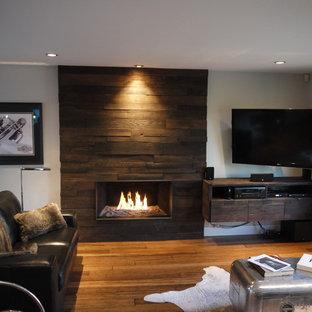 Imagen de salón abierto, rústico, de tamaño medio, con paredes blancas, suelo de bambú, chimenea tradicional, marco de chimenea de madera y televisor colgado en la pared