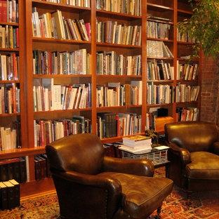 Immagine di un soggiorno classico di medie dimensioni e chiuso con libreria, pareti rosse, parquet scuro, nessun camino, nessuna TV e pavimento marrone