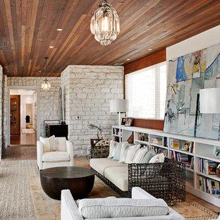 Idee per un soggiorno design con libreria e pavimento in mattoni