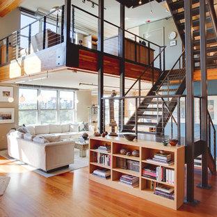 Esempio di un grande soggiorno industriale stile loft con pavimento in legno massello medio, nessun camino, nessuna TV e pareti beige