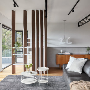 This is an example of a contemporary open concept living room in Melbourne with white walls and beige floor.