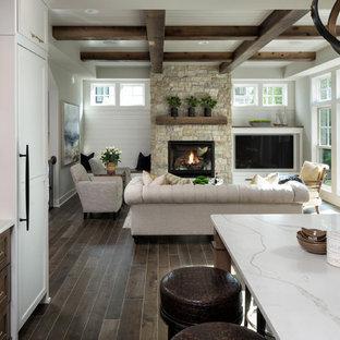Inredning av ett klassiskt stort allrum med öppen planlösning, med ett finrum, grå väggar, mörkt trägolv, en standard öppen spis, en spiselkrans i sten, en inbyggd mediavägg och brunt golv